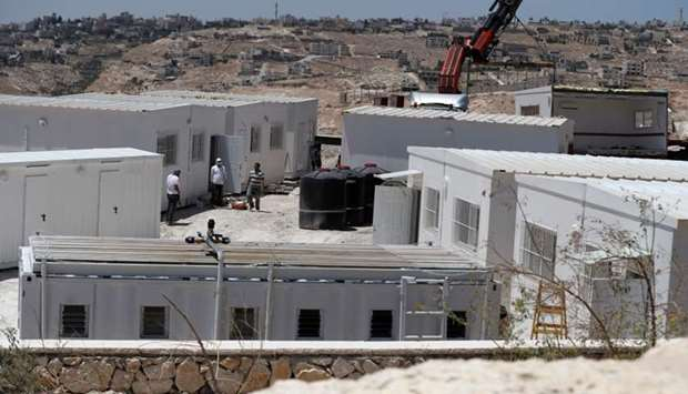 Israeli workers place container houses near the town of Al-Eizariyah in the occupied West Bank near