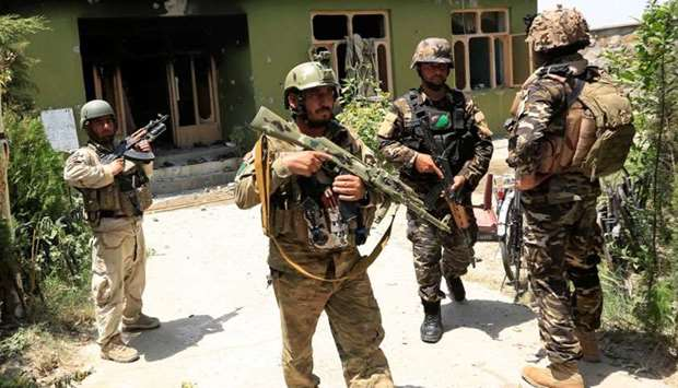 Afghan security forces personnel inspect a site after an attack