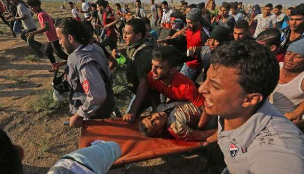 Palestinian paramedics and protester carry a killed protester away from clashes with Israeli forces