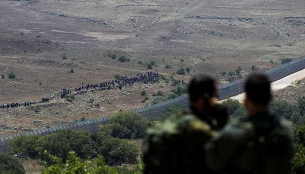 Israeli soldiers look on towards people standing next to the border fence between Israel and Syria f