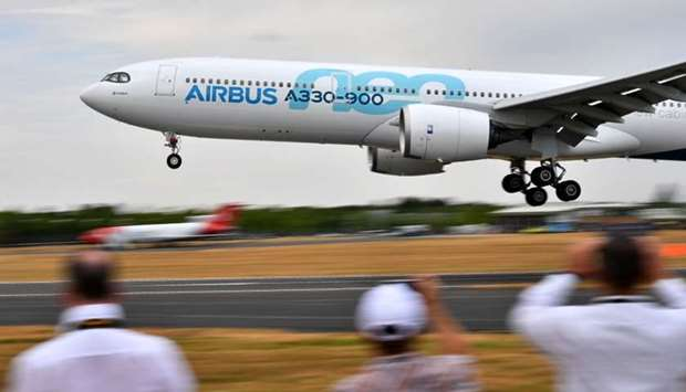 Visitors watch as an AirBus A330-900 Neo lands during