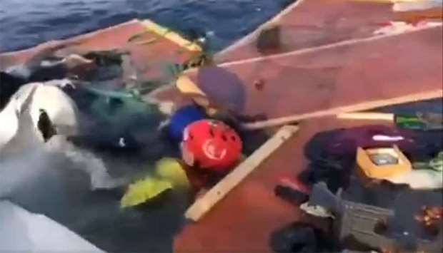 A member of the rescue team (wearing red helmet) of  Proactiva Open Arms searches the wreckage of a
