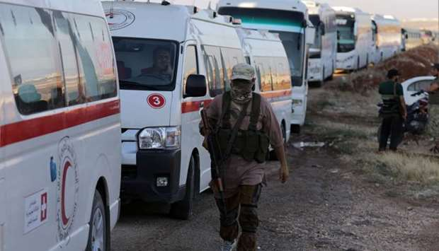 Rebels from Hayat Tahrir al-Sham are seen yesterday near ambulances and buses outside the villages o