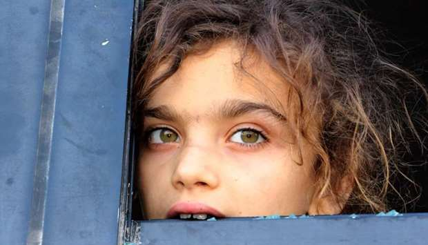 An evacuated Syrian girl from the area of Fuaa and Kafraya in the Idlib province, looks out of a bro