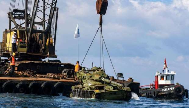 Environmental activists drop off an old battle tank provided by the Lebanese Armed Forces into the M