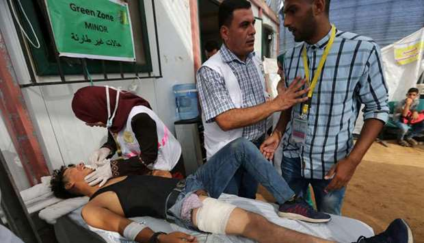 A medic tends to a wounded Palestinian during a protest at the Israel-Gaza border, in the southern G