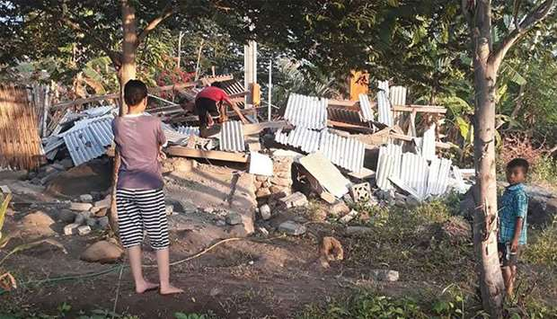 An Indonesian person (C) scrambling over the collapsed ruins of a house as others look on following