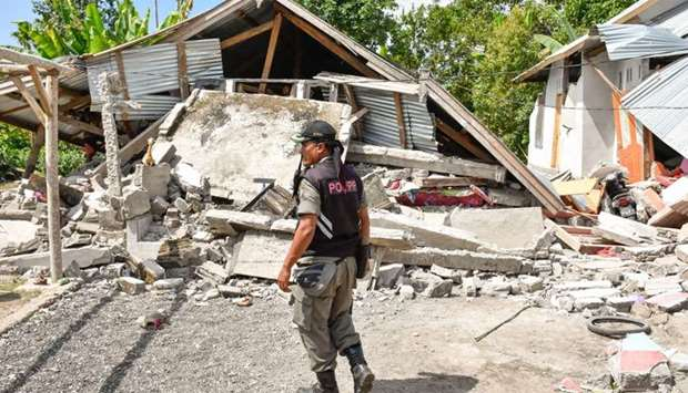 An Indonesian village security officer examines the remains of houses, after a 6.4 magnitude earthqu