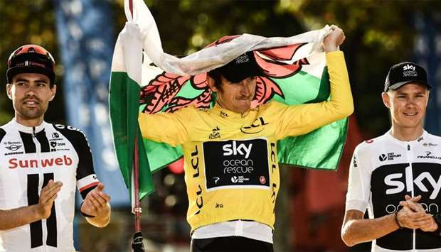 Tour de France 2018 winner Great Britain's Geraint Thomas (C), holds a Welsh flag and the overall le