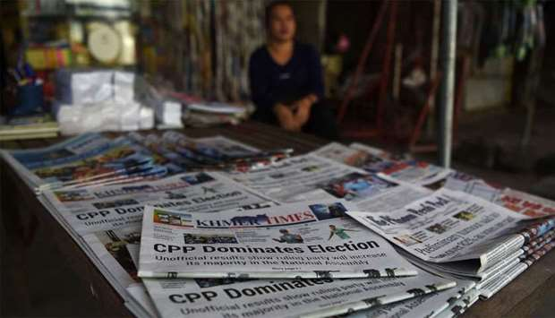 A vendor waits for customers with newspapers featuring reports on Prime Minister Hun Sen's ruling Ca