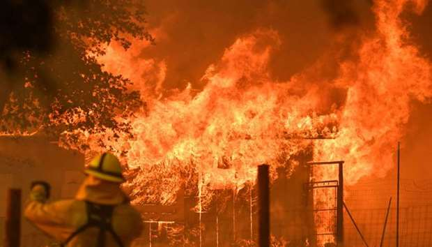 A firefighter watches as a building burns during the Mendocino Complex fire in Lakeport, California