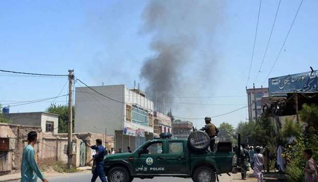 Afghan security personnel secure a road as smoke billows from the site of suicide attack as an ongoi