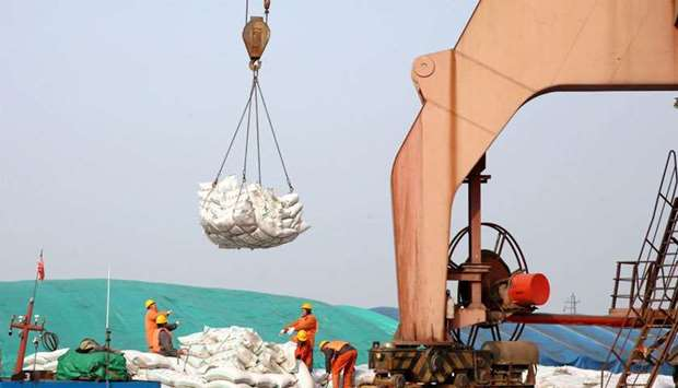 Chinese workers transferring bags of soybeans at a port in Nantong in China's eastern Jiangsu provin