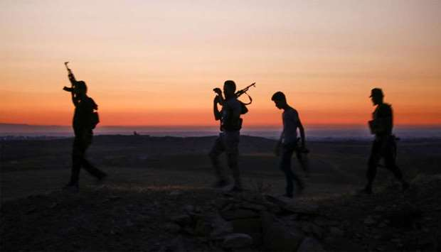 Syrian rebel fighters walk with their arms near the frontline against government forces west of the