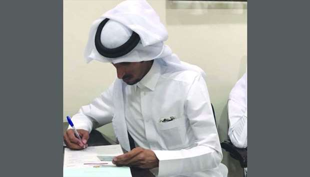 An official checks documents at a shop in Aziziya