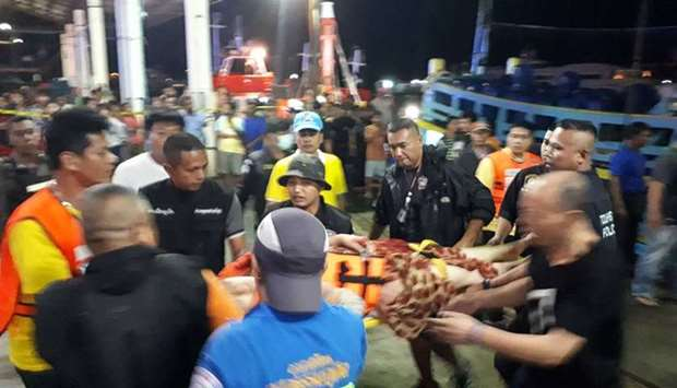 Thai rescue and paramedic personnel attend to rescued passengers of capsized tourist boat in rough s