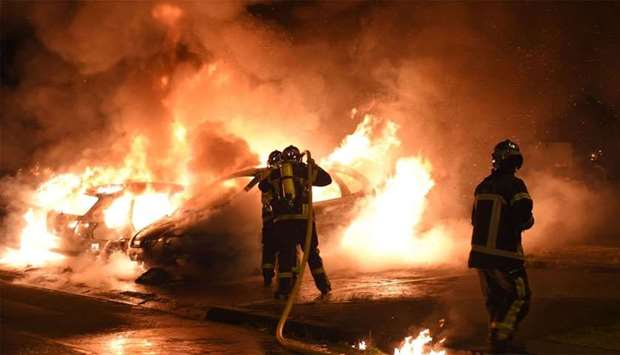 Firefighters work to put out a fire as cars burn in the Le Breil neighborhood of Nantes.