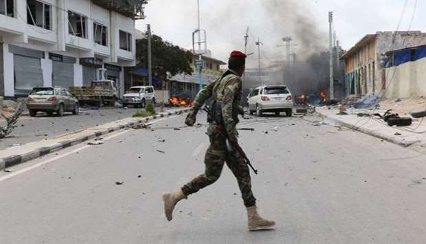 A Somali military officer runs to secure the scene of a suicide car bombing near Somalia's president