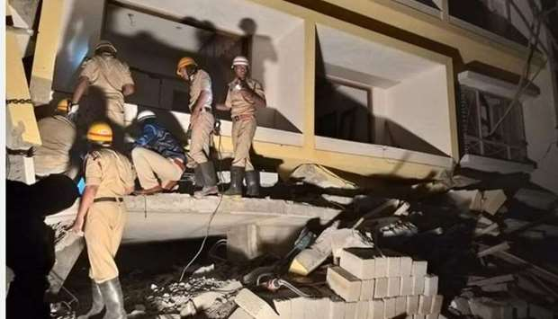 Fire and rescue personnel look for people inside the collapsed Bengaluru building.