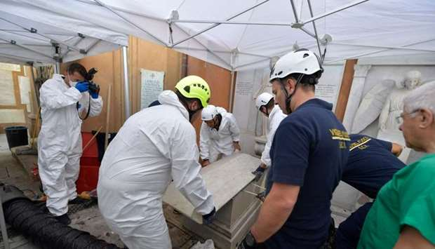 Forensics (L) and firefighters (R) opening of one of two tombs within the Vatican's grounds in the T