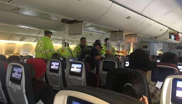 Emergency workers assist passengers of Air Canada AC 33 flight, which diverted to Hawaii after turbu