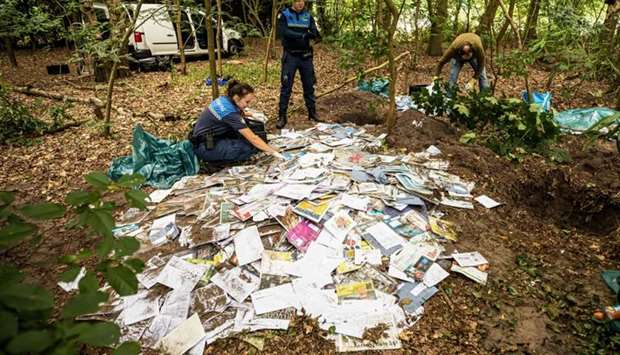 Dutch police officers stand near thousands of excavated postal items from postal company Sandd, at R