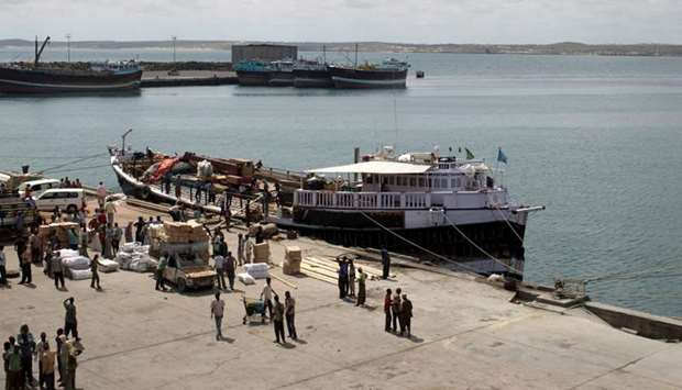 Workers stand at the sea port of the coastal town of Kismayu in southern Somalia.