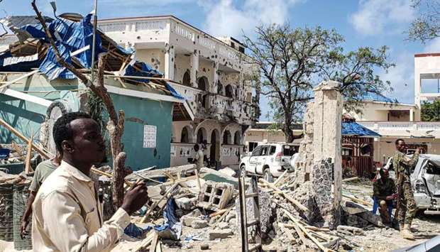 A man passes in front of the rubbles of the popular Medina hotel of Kismayo