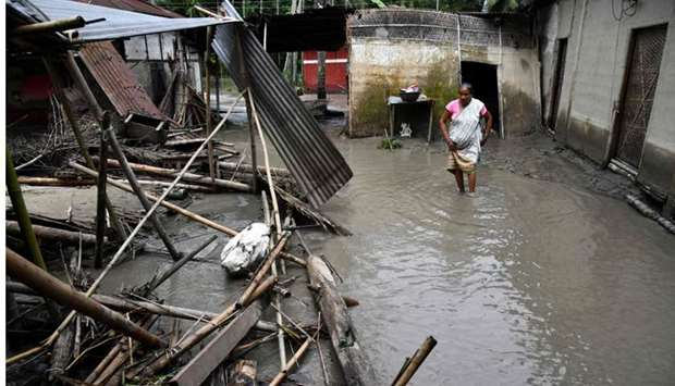 An Indian woman searches her belongings near the debris of her house following floodwaters in Kasuar