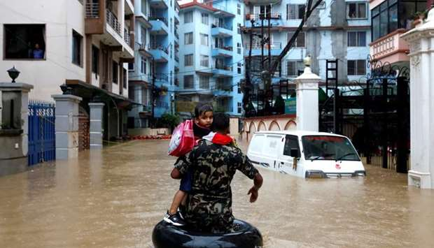 A member of Nepalese army carrying a child walks along the flooded colony in Kathmandu, Nepal July 1