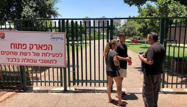 A security guard checks the identification of visitors near the entrance to a park in the northern I