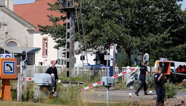French gendarmes stand at a level crossing after a car and a TER regional express train crashed at t
