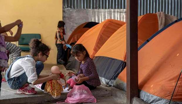 Minor migrants play next to tents piled up in a hangar at Juventud 2000 migrant shelter in Tijuana,