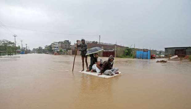 Villagers use a makeshift raft to cross a flooded area on the outskirts of Agartala, India