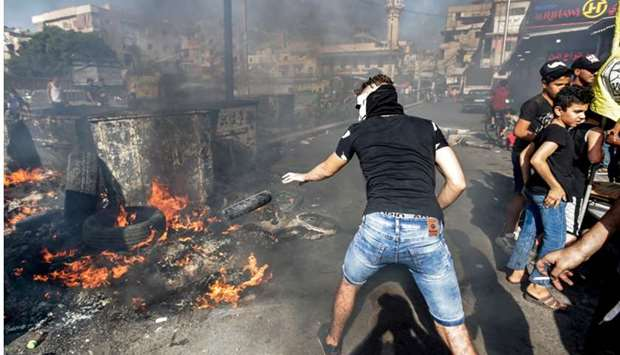 A masked man throws a tire into a fire as protesters block the main road outside the Palestinian ref