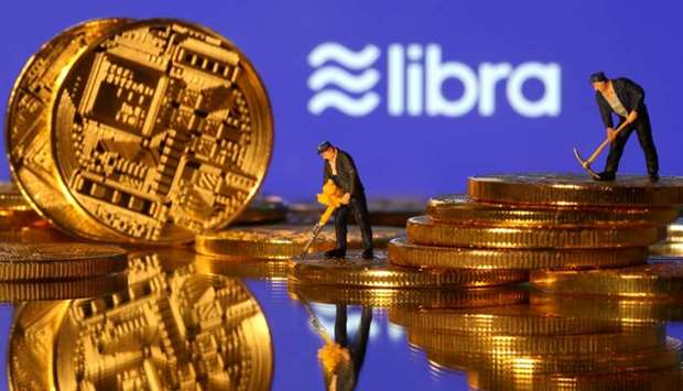 Small toy figures are seen on representations of virtual currency in front of the Libra logo in this