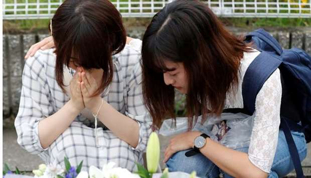 Women pray in front of a row bouquets placed out for victims of the torched Kyoto Animation building