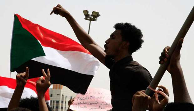 A Sudanese protester chants slogans as others wave national flags in the capital Khartoum's Green Sq