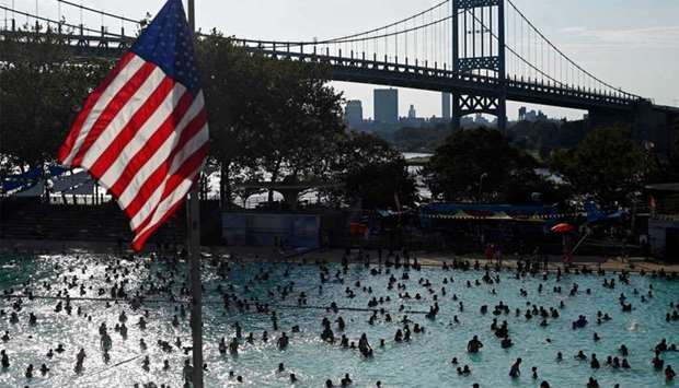 A US flag flies overhead as people enjoy the Astoria Pool on a hot afternoon in the borough of Queen