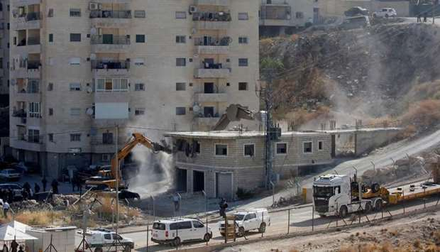 Israeli security forces tearing down one of the Palestinian buildings still under construction in th
