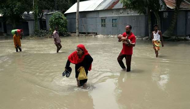 People cross a flooded road in Jamalpur, Bangladesh