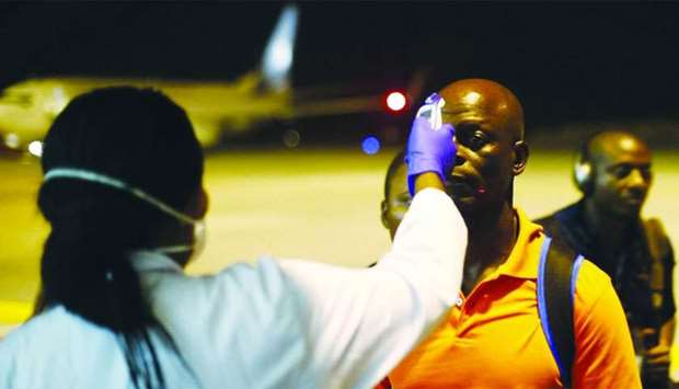 A health worker checks the temperature of a man arriving at Bata Airport in Litoral, Equatorial Guin