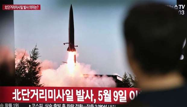 A man watches a television news screen showing a file footage of a North Korean missile launch, at a