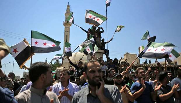 Syrian men wave rebel flags as they demonstrate in Azaz, north of Aleppo.