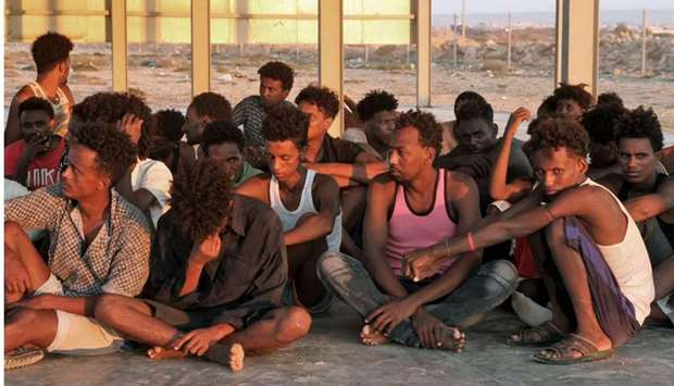 Rescued migrants sit on the coast of Khoms, some 100 kilometres from Tripoli