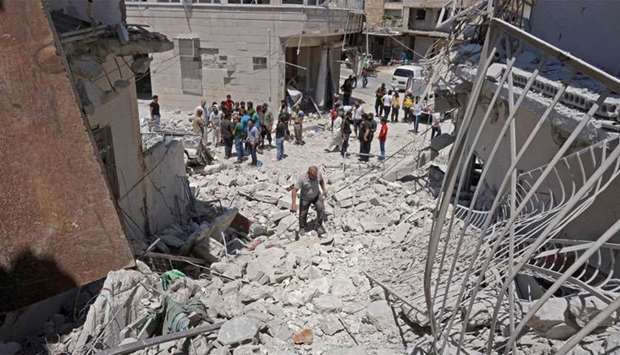 Syrians gather at the site of a reported air strike on the town of Ariha