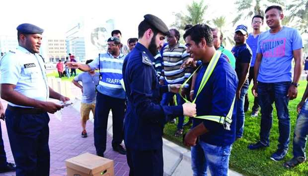 Officials helping pedestrians wear a reflecting jacket during an awareness programme.