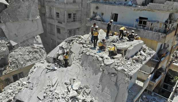 Members of the Syrian Civil Defence (White Helmets) search for victims at the site of a reported air