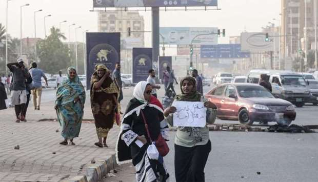 "Sudanese protesters carry a placard during a rally in the capital Khartoum to condemn the ""massacre"""