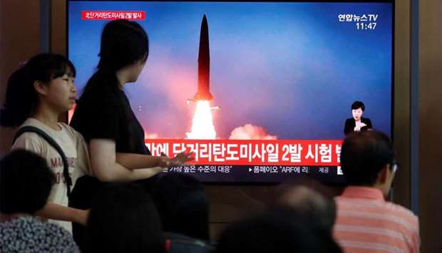 People watch a TV that shows a picture of a North Korean missile for a news report on North Korea fi